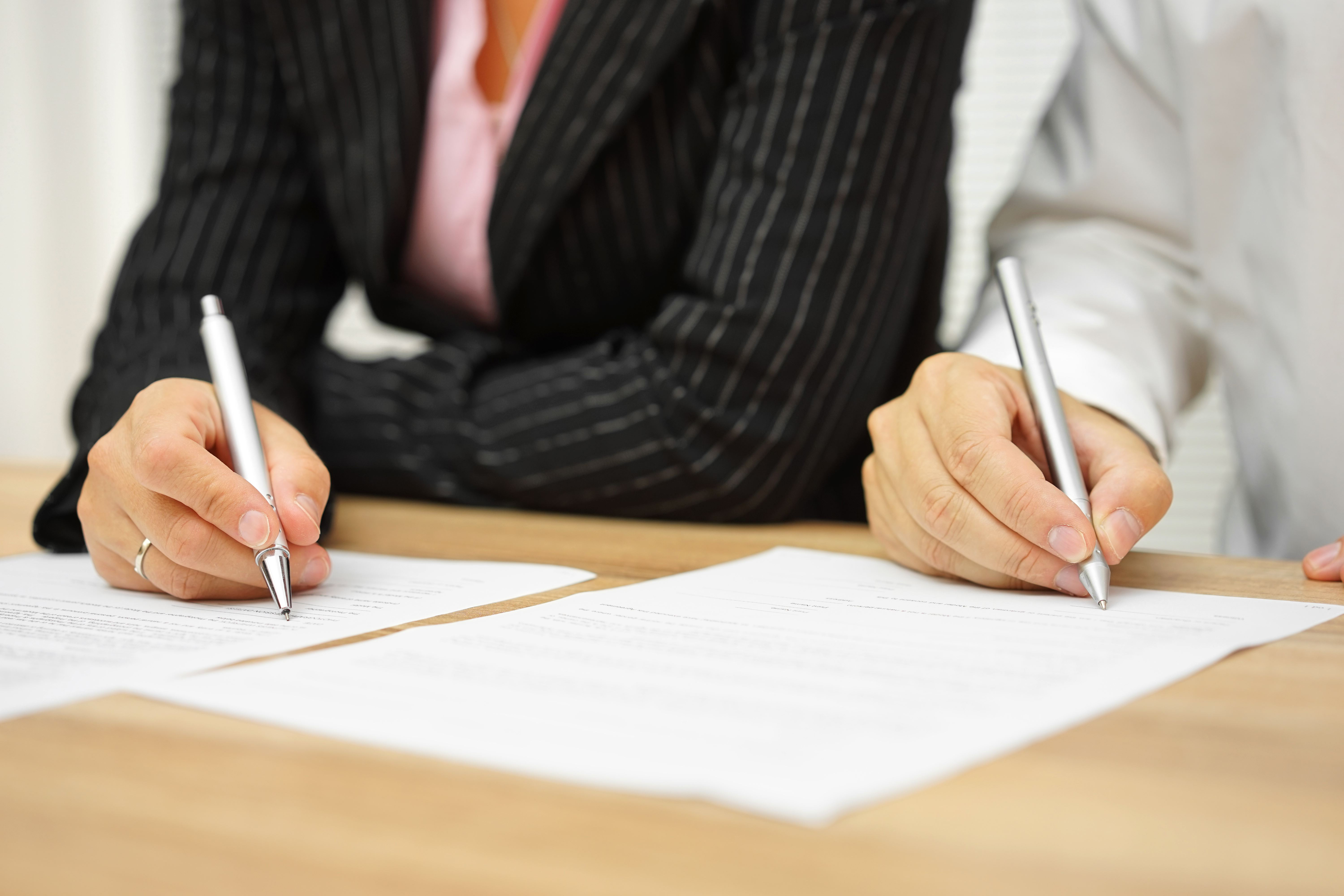 Man and woman signing papers - grounds for legal separation